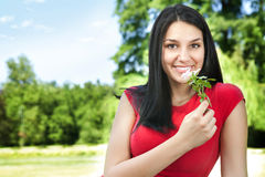 Smiling young woman with flower Stock Image