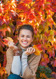 Smiling young woman in front of autumn foliage Stock Photo