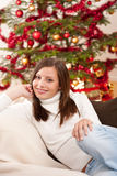 Smiling young woman in front of Christmas tree Stock Photography