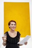 Smiling young woman in front of yellow wall painting Royalty Free Stock Photography