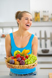 Smiling young woman with fruits plate in kitchen Royalty Free Stock Photos