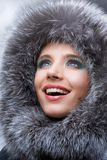 Smiling young woman with a fur hood Stock Photo