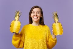 Smiling young woman in fur sweater looking aside holding halfs of fresh ripe pineapple fruit isolated on violet pastel royalty free stock images
