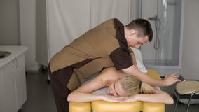 Smiling Young Woman Getting Massage Treatment From Masseuse. Professional techniques stock footage
