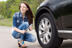 Smiling young woman getting ready to change a tyre Stock Photo