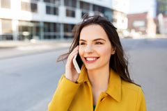 Smiling young woman or girl calling on smartphone stock images