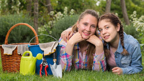 Smiling young woman and girl with gardening tools in outdoors stock images
