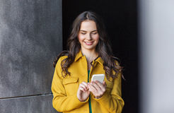 Smiling young woman or girl texting on smartphone Royalty Free Stock Photography