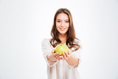 Smiling young woman giving apple at camera Royalty Free Stock Images