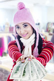 Smiling young woman giving dollar bills. Young woman giving US dollar bills cheerfully wearing winter outfit Stock Photo