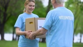 Smiling young woman giving donation box to senior volunteer, assistance project. Stock footage stock video footage