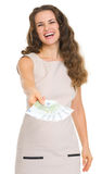 Smiling young woman giving fun of euro banknotes Stock Photo