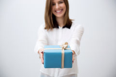 Smiling young woman giving gift Stock Photos
