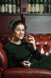 Smiling young woman with a glass of brandyf brandy Royalty Free Stock Photography