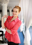 Smiling young woman with glasses in hotel restaurant Royalty Free Stock Photo