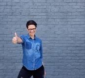 Smiling young woman with glasses showing thumbs up sign Royalty Free Stock Image