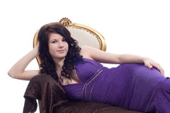 Smiling young woman on golden chair Royalty Free Stock Images