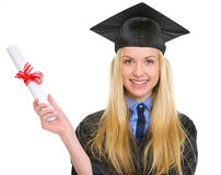 Smiling woman in graduation gown holding diploma Stock Photography