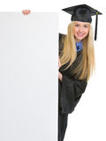 Girl in graduation gown looking out from billboard. Smiling young woman in graduation gown looking out from blank billboard royalty free stock photography