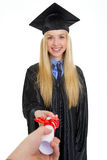Smiling woman in graduation gown receiving diploma Stock Image