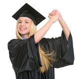 Smiling woman in graduation gown rejoicing success Royalty Free Stock Images