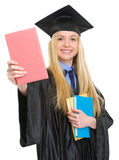 Smiling woman in graduation gown showing book Stock Photo