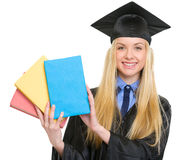 Smiling woman in graduation gown showing books Royalty Free Stock Image