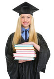 Woman in graduation gown with stack of books Stock Photography