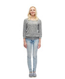 Smiling young woman in gray pullover and jeans Royalty Free Stock Images