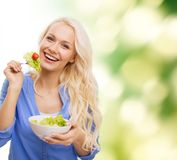 Smiling young woman with green salad Royalty Free Stock Photos