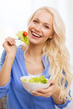 Smiling young woman with green salad at home Royalty Free Stock Photo