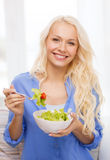 Smiling young woman with green salad at home Royalty Free Stock Image