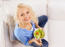 Smiling young woman with green salad at home Stock Images