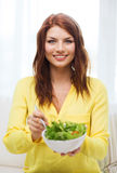 Smiling young woman with green salad at home Stock Photo
