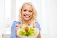 Smiling young woman with green salad at home Royalty Free Stock Images