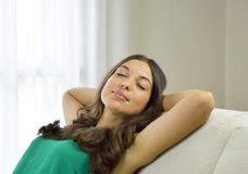 Smiling young woman with green tank top relaxing on a sofa at home sitting on a sofa in the living room royalty free stock image