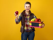 Smiling young woman grower with box of apples showing an apple. Healthy food to your table. Portrait of smiling young woman grower in checkered shirt isolated on Royalty Free Stock Images