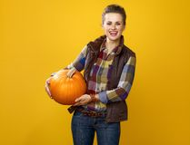Smiling young woman grower on yellow background holding pumpkin. Healthy food to your table. Portrait of smiling young woman grower in checkered shirt on yellow Royalty Free Stock Photography
