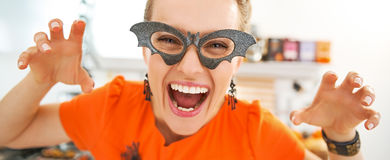 Smiling young woman in Halloween decorated kitchen frightening. Frightful Treats all the way. smiling young woman in party bat glasses in the Halloween decorated stock images