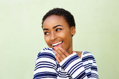 Smiling young woman with hand over mouth Stock Photos