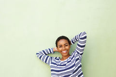 Smiling young woman with hands behind head Stock Image