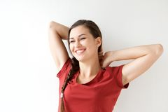 Smiling young woman with hands behind head on white background. Portrait of smiling young woman with hands behind head on white background Stock Images