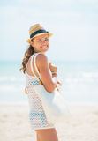 Smiling young woman in hat and with bag on beach Stock Images
