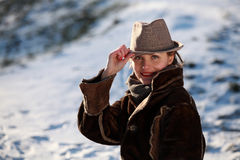 Smiling young woman with hat. Beautiful young woman in a park in winter time royalty free stock photography