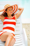 Smiling young woman in hat laying on sunbed. Portrait of smiling young woman in hat laying on sunbed Royalty Free Stock Photo