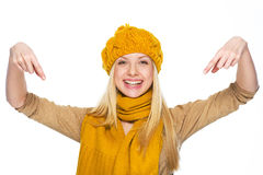 Smiling young woman in hat and scarf pointing down on copy space Royalty Free Stock Photography
