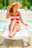 Smiling young woman in hat sitting on sunbed Royalty Free Stock Photos