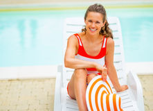 Smiling young woman in hat sitting on sunbed Stock Photo