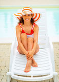 Smiling young woman in hat sitting on sunbed Royalty Free Stock Photography