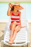 Smiling young woman in hat sitting on sunbed Royalty Free Stock Photo